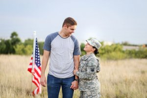 Happy military couple and flag