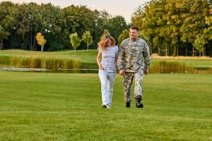 Soldier and his girlfriend are walking on the grass