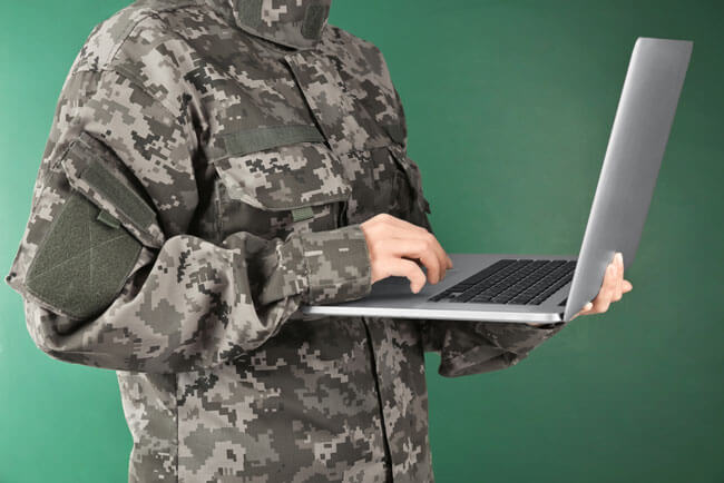 Soldier holding laptop and write